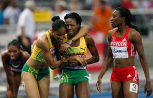 Melaine Walker (centre) and teammate Kaliese Spencer react after her 400 m hurdles victory. Trinidad's bronze medallist Josanne Lucas is at right. / Photo credit: AP